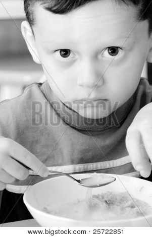 Young boy looking unhappy while eating healthy cereal