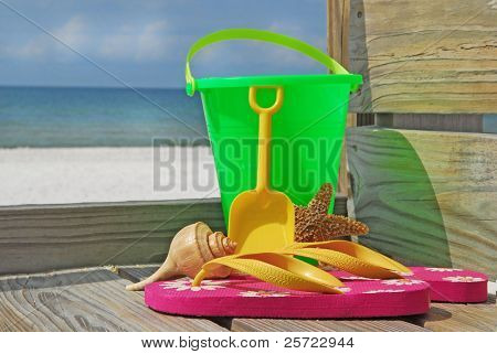Collection of colorful beach toys and flip flops at seashore