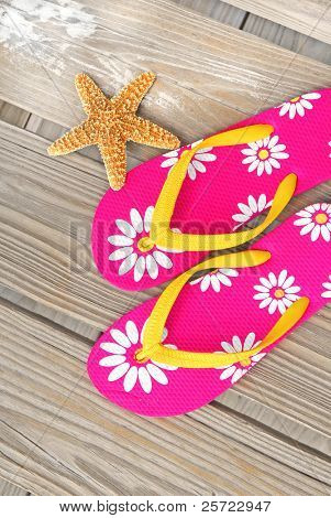 Pretty flip flop sandals on beach dock by starfish