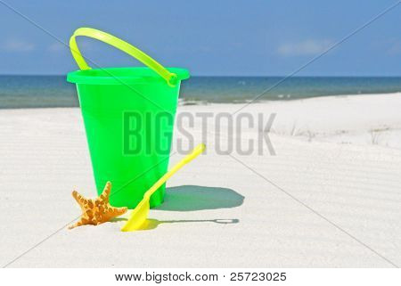 child's beach bucket by starfish at seashore
