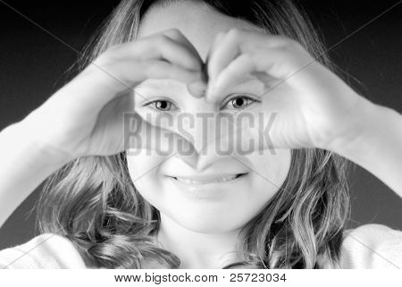 Happy young girl making heart shape out of hands
