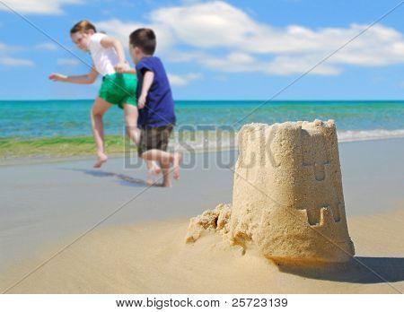 happy children running on beach by sand castle