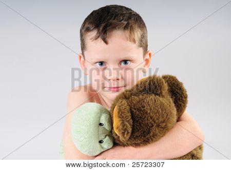 Young boy with big blue eyes cuddling stuffed animals