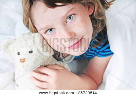 Young girl looking happy in comfortable bed