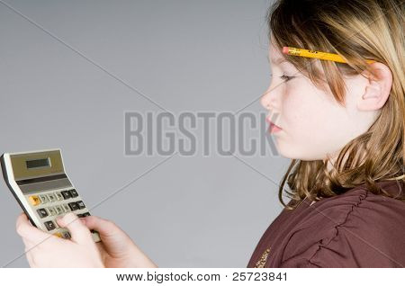 Young girl with calculator working on math
