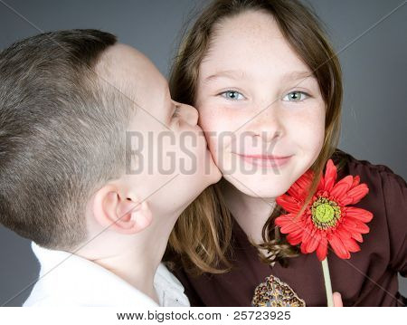 Young boy kissing girl after giving her flower