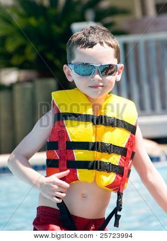 Young boy in pool wearing safety flotation