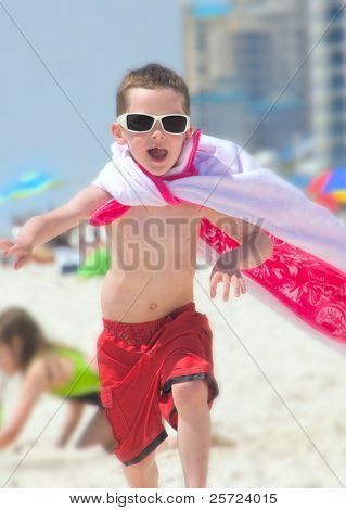 Young boy on beach pretending to be superhero