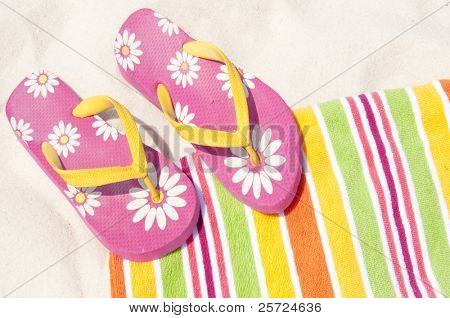 colorful flip flops on beach towel