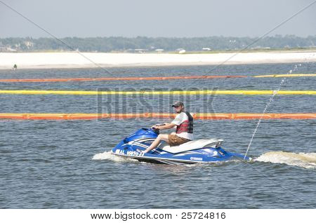 ORANGE BEACH, AL- JUNE 8: A recreational boater motors past protective oil boom positioned in Perdido Pass on June 8, 2010 in an effort to protect Orange Beach, AL from the BP oil spill.