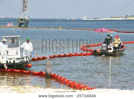 PENSACOLA - JUNE 10:  Oil spill workers clean the beach of Naval Air Station Pensacola, FL as oil washes ashore from the BP spill on June 10, 2010 in Pensacola, Florida.