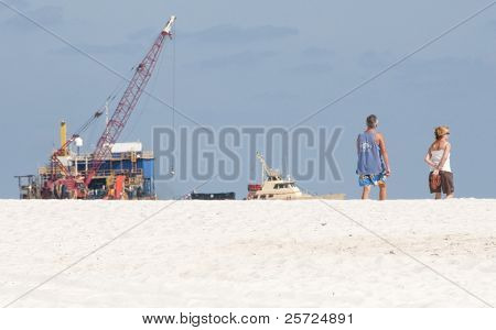 ORANGE BEACH, AL - JUNE 10:  Tourists stroll past huge oil spill machinery in place at Peridido Pass, AL on June 10, 2010 as oil washes ashore.