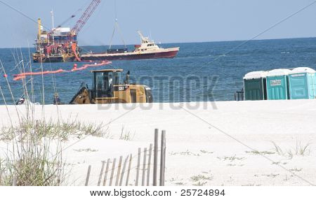 ORANGE BEACH, AL - JUNE 10: Tractors deliver portable toilets to service oil spill workers at Perdido Pass, AL on June 10, 2010 as oil washes ashore as oil containment efforts continue (background).