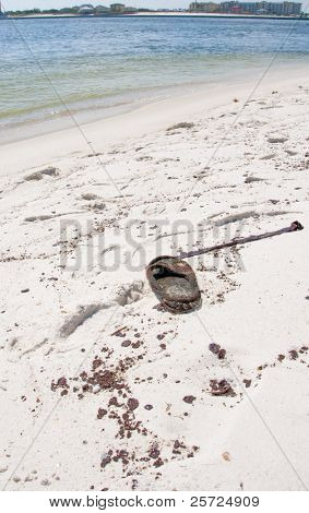ORANGE BEACH, AL - JUNE 10: An oil soaked flip flop next to a large area of thick black oil splotches at Perdido Pass on June 10, 2010 as the BP oil spill washes ashore.