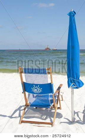 ORANGE BEACH, AL - JUNE 10: Empty beach chair on June 10, 2010 at the height of tourist season at Perdido Pass, AL as the tourism industry suffers from the oil spill (clean up efforts in background).