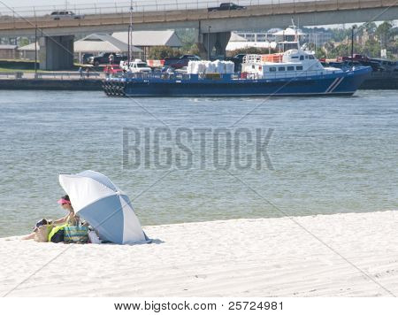 ORANGE BEACH, AL - JUNE 10:  Lone beach goer sits on beach of Perdido Pass, AL on June 10, 2010 as an oil spill boat cruises past BP oil spill staging area in distance.