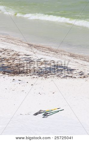 PENSACOLA BEACH - JUNE 23:  Oil covered sand is shown on June 23, 2010 in Pensacola Beach, FL. BP worker shovels lie in the foreground.