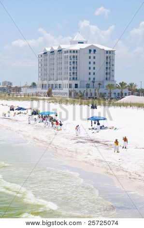 PENSACOLA BEACH - JUNE 23:  BP oil workers work as oil washes ashore on Pensacola Beach, FL on June 23, 2010. Jimmy Buffet's new Margaritaville Hotel opening soon in background.