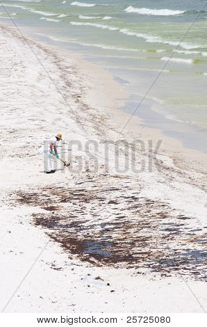 PENSACOLA BEACH - JUNE 23:  A BP oil worker attempts to clean oil covered sand on June 23, 2010 in Pensacola Beach, FL.