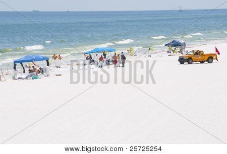 PENSACOLA BEACH - JUNE 23:  BP oil workers and skimmer boats attempt to clean oil covered sand on June 23, 2010 in Pensacola Beach, FL.