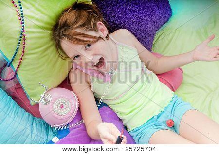Happy girl polishing nails on phone