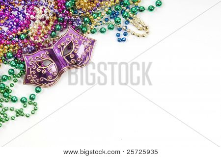 Mardi gras mask and beads in pile