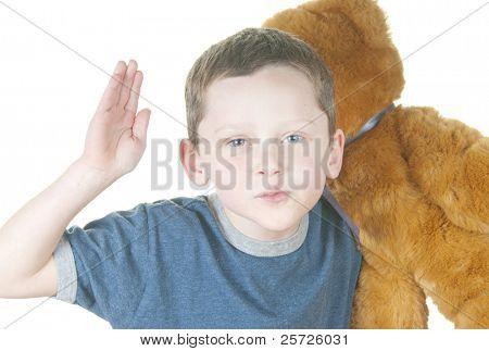Young boy acting tough holding bear