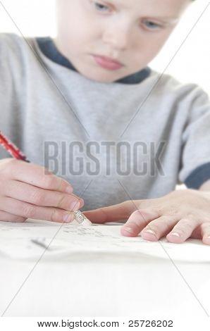 Shallow focus on pencil of boy erasing mistake