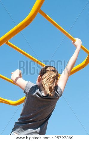 girl crossing elevated monkey bars