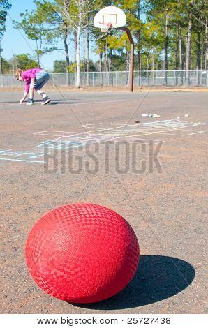 ball on playground with giirl writing chalk
