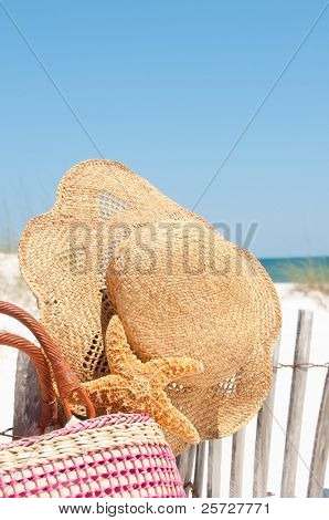 hat and bag on beach fence