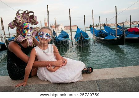 Carnival in Venice, Italy. Portrait of two beautiful girls. Gondolas and San Giorgio Maggiore church in background