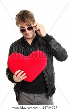 Valentines day man player holding heart looking over sunglasses. Funny image of caucasian male in leather jacket isolated on white background.