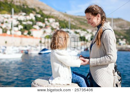 Portrait of mother and daughter outdoors on sunny autumn or spring day