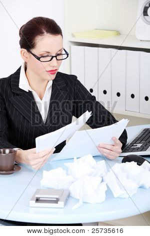 Pretty caucasian businesswoman reading files near crumpled files in the office.