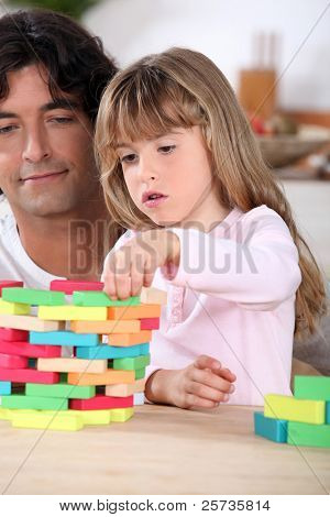 Father and daughter playing a game at home
