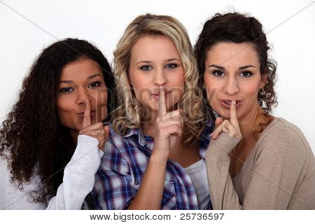 Three women making shush gesture