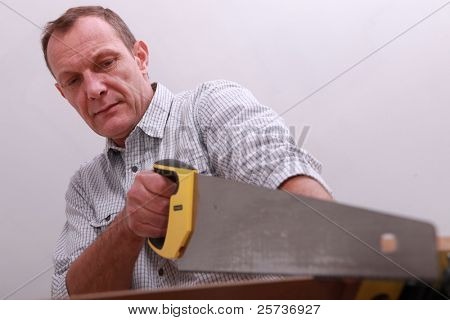 Middle-aged carpenter using hand-saw