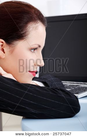 Pretty caucasian thinking businesswoman lying on the desk in the office.