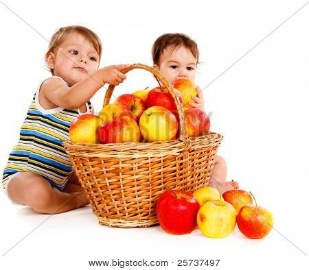 Two cheerful children playing with apples basket