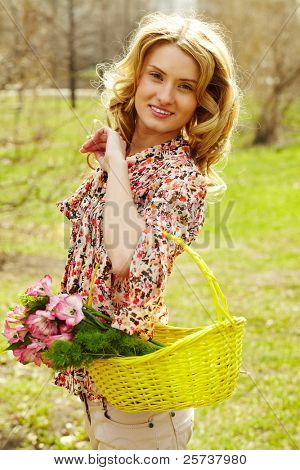 Girl holding a basket with flowers and looking at camera