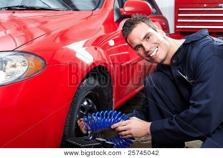 Professional auto mechanic changing tire in auto repair shop. Garage.