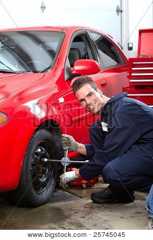 Professional auto mechanic changing tires in auto repair shop. Garage.