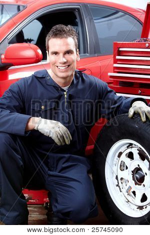 Professional auto mechanic changing a tire in auto repair shop. Garage.