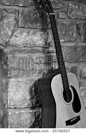 Rustic black and white image of a steel-stringed acoustic guitar leaning against a stone wall.