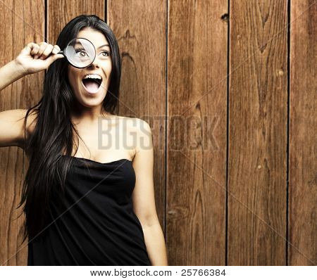 young woman looking through a magnifying glass against a wooden wall