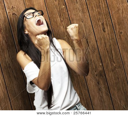 portrait of young woman doing good symbol against a wooden wall woman win gesture against a wooden wall