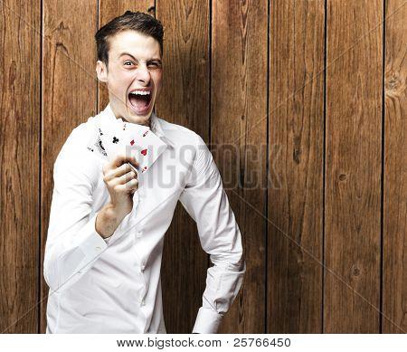 retrato de jovem gritando com megafone contra um homem de madeira da parede, segurando cartas de poker contra