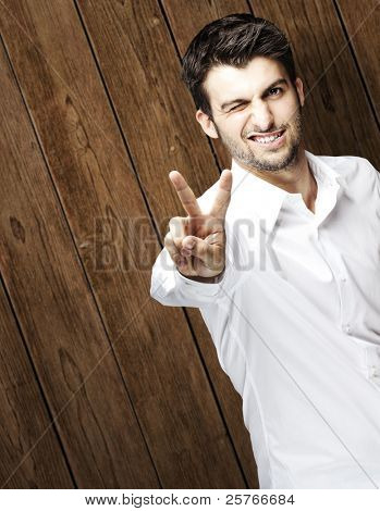 portrait of young man doing good symbol against a wooden wall