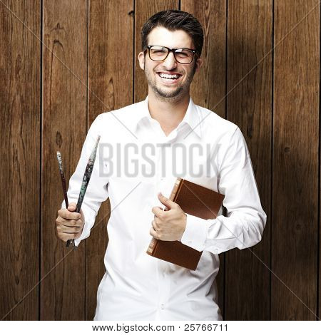 portrait of young man holding books against a wooden wall